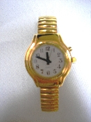 "This high fashion polish gold tone quality watch has a clear voice, with an easy to see 1"" white face with bold black numbers and large black hands. A female voice states the time at the touch of a button."